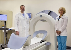 Cardiologist Dr. James Mohn and CNMT Lead Nuclear Medicine Technologist Caroline Edland stand by the Discovery™ NM 530 nuclear imaging system